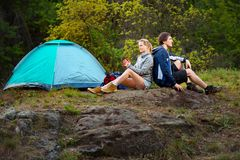 Couple hikers in the wild forest. Man and woman resting with cup. Couple hikers in the wild forest. Man and women resting with cup of tea near the tent. Travel Royalty Free Stock Images