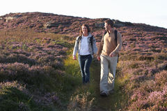 Couple Hiking Across Moorland Covered With Heather Royalty Free Stock Photography