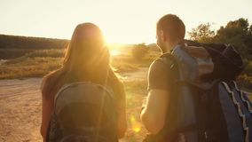 Couple hiking with backpacks at sunset stock video footage