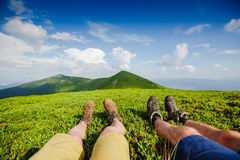 Couple in hiking boots having fun and enjoying wonderful breathtaking mountain view. Travel trekking leisure holiday concept. Couple in hiking boots having fun Royalty Free Stock Photography