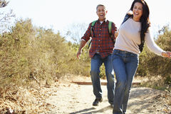 Couple Hiking In Countryside Wearing Backpacks Royalty Free Stock Photography
