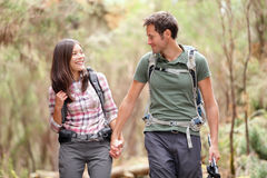 Couple hiking happy. Young couple hiking in forest looking happy. Man and woman hikers holding hands walking in nature. From Aguamansa, Tenerife, Spain Royalty Free Stock Image