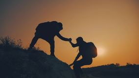 Couple hiking help each other silhouette in mountains. Teamwork couple hiking, help each other, trust assistance, sunset. Man giving hand a woman to help her stock video footage