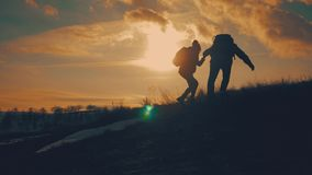 Couple hiking help each other silhouette in mountains. Teamwork couple hiking, help each other, trust assistance, sunset stock footage