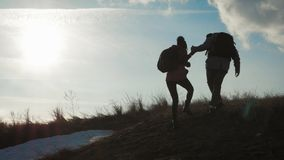 Couple hiking help each other silhouette in mountains. Teamwork couple hiking, help each other, trust assistance, sunset. Man giving hand a woman to help her stock footage