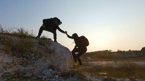Couple hiking help each other silhouette in mountains. Teamwork couple hiking, help each other, trust assistance, sunset. Man giving hand a woman to help her stock video