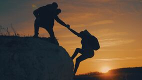 Couple hiking help each other silhouette in mountains. Teamwork couple hiking, help each other, trust assistance, sunset