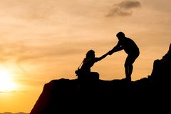 Couple hiking help teamwork and trust silhouette in mountains, s royalty free stock images