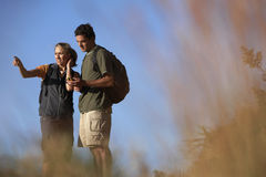Couple hiking, man holding navigation system, woman pointing, focus on background Stock Images