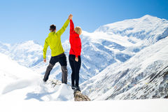 Couple hiking man and woman success in winter mountains. Couple hikers men and women success in winter mountains, sport climbing. Inspiration and motivation in Royalty Free Stock Photos