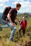 Couple hiking in mountains. A young male hiker is helping a female hiker to climb a mountain in the German Alps near Oberstdorf royalty free stock image