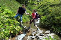 Couple hiking in mountains. A young male hiker is helping a female hiker to cross a mountain-brook in the German Alps near Oberstdorf royalty free stock image