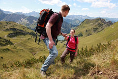 Couple hiking in mountains. A young male hiker is helping a female hiker to climb a mountain in the Alps stock photo
