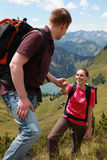 Couple hiking in mountains. A young male hiker is helping a female hiker to climb a mountain in the Germen Alps stock images