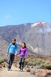 Couple hiking outdoors. In nature. Happy young couple hikers walking outside in dramatic mountain landscape on volcano Teide, Tenerife, Canary Islands Royalty Free Stock Photo