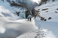 Couple hiking outdoors with backpacks in winter mountains. Travel concept.  Royalty Free Stock Photo