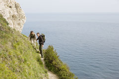 Couple Hiking On A Path Above The Water Royalty Free Stock Images