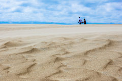 Couple Holding Hands Strolling on Top of Sand Dunes. Textured sand highlights the foreground of this photo with a couple holding hands strolling along the top of Stock Image