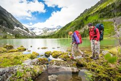 Couple is hiking on trail at the lake in mountains of Altai Stock Image