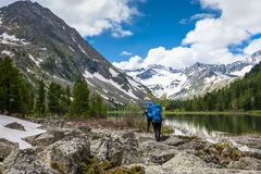 Couple is hiking on trail at the lake in mountains of Altai Stock Photos