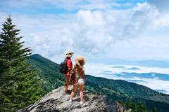 Couple on hiking trip, standing on top of the mountain over the clouds. Looking at beautiful summer mountain landscape. People enjoying beautiful view. Close stock images