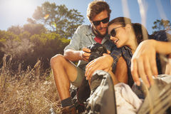 Couple on hiking trip taking a break sitting and looking at pict Stock Photography