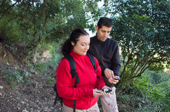 Couple hiking using compass and phone map stock images