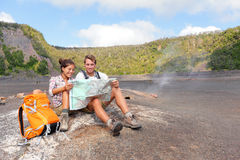 Couple hiking on volcano on Hawaii looking at map. Happy young men and women relaxing taking break in beautiful volcanic landscape nature on Big Island in Stock Photo