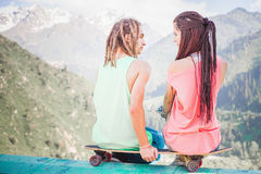 Couple of hipster, young people at mountain with longboard skateboard. World Day of skateboarding stock photos