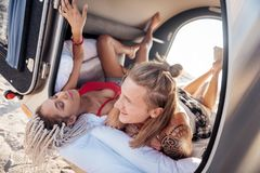 Couple of hipsters chilling lying in compact trailer traveling on it together. Couple of hipsters. Couple of good-looking stylish hipsters chilling lying in stock images