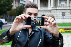 Couple of Hipsters Having Fun with Smartphone Photography Stock Photography