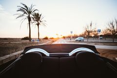 Couple hipsters in love ride convertible in summer. Backseat view from back of convertible cabriolet car during beautiful and epic sunset with palm trees and royalty free stock photos