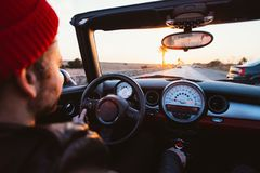 Couple hipsters in love ride convertible in summer. Middle age hipster man with beard and small red beanie hat drives convertible cabriolet car with open roof Royalty Free Stock Photography