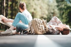 Young happy family spend time together on outdoor. Couple of hipsters traveling with backpack adventure vacations sitting and rest on e of the road. Lifestyle stock images
