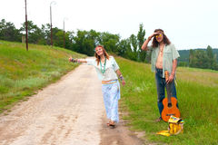 Couple hitchhiker hippie on the road Stock Images