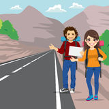 Couple Hitchhiking. Couple with backpack hitchhiking standing on road side Royalty Free Stock Photos