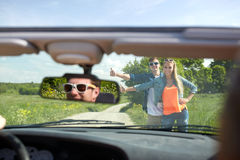 Couple hitchhiking and stopping car on countryside. Road trip, hitchhike, travel, gesture and people concept - happy couple hitchhiking and stopping car at Royalty Free Stock Photography