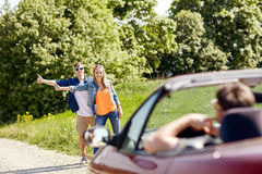 Couple hitchhiking and stopping car on countryside. Road trip, hitchhike, travel, gesture and people concept - happy couple hitchhiking and stopping car at Royalty Free Stock Image