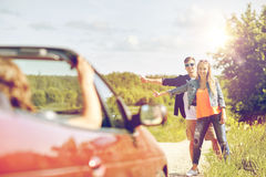Couple hitchhiking and stopping car on countryside. Road trip, hitchhike, travel, gesture and people concept - happy couple hitchhiking and stopping car at Stock Photography