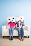 Couple hold billboard. And sit on sofa at home Stock Photography