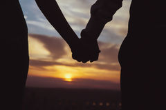 The couple that hold each other's hand watch the sunset. stock photo