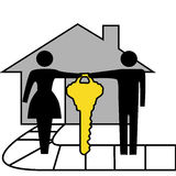 Couple hold gold house key to family home. A couple hold a gold house key to family home Royalty Free Stock Images