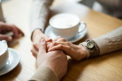 Couple hold hands drinking coffee in cafe, close up of lovers arms on background of wooden table. Breakfast or lunch in restaurant royalty free stock photo