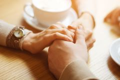 Couple hold hands drinking coffee in cafe, close up of lovers arms on background of wooden table. Breakfast or lunch in restaurant stock images