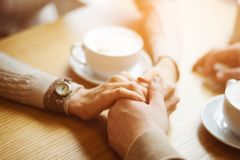 Couple hold hands drinking coffee in cafe, close up of lovers arms on background of wooden table. Breakfast or lunch in restaurant royalty free stock images