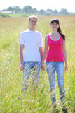 Couple hold hands in field near village Royalty Free Stock Images