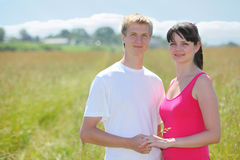 Couple hold hands, grass in field near village Stock Photography