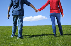 Couple hold hands and walks on a green grass to the horizon stock images