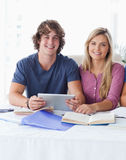 A couple hold a tablet together. While looking into the camera Stock Images