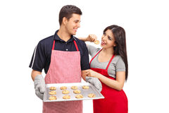 Couple holding an aluminum pan with cookies Royalty Free Stock Photos